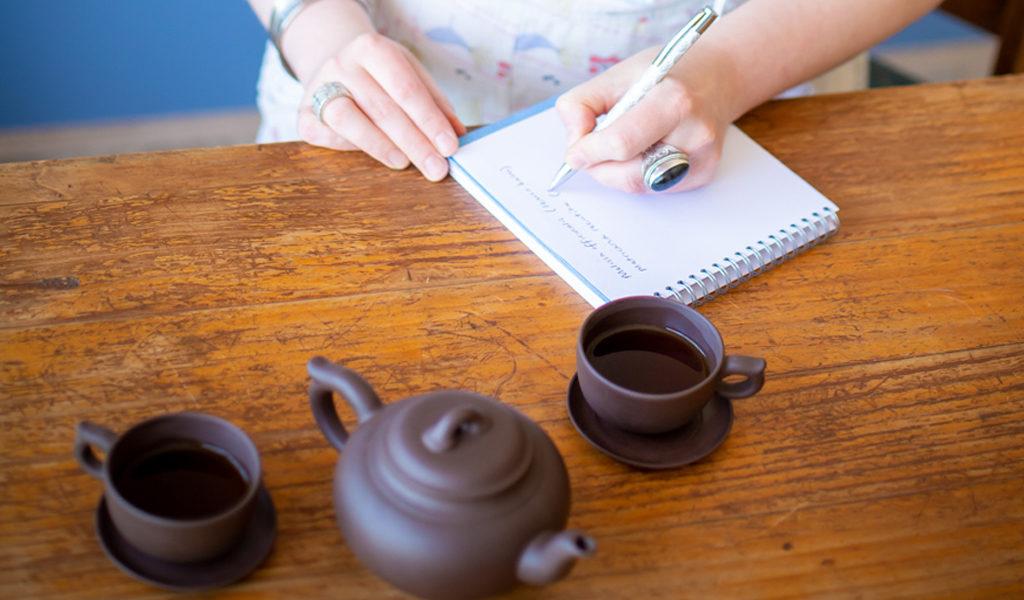 Karla Rawles, Naturopath, writing notes and drinking tea