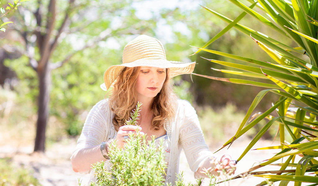 Karla Rawles, Naturopath, picking fresh rosemary in her Newstead garden