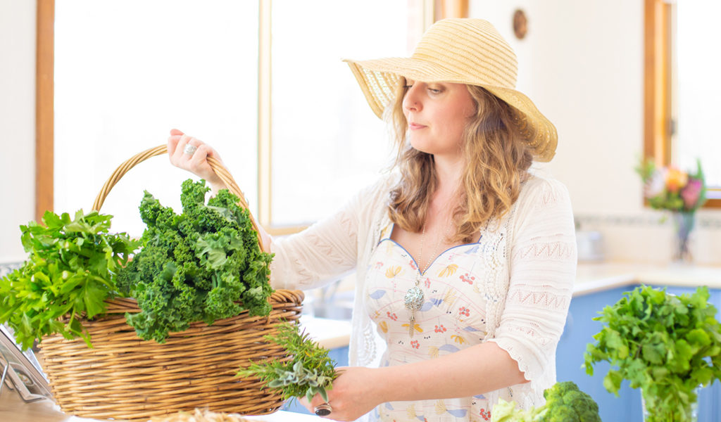 Karla Rawles, Naturopath, carrying a basket of green vegetables